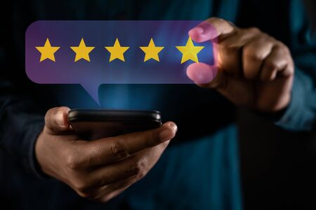 Customer Experiences Concept. a Modern Man Giving Five Stars Rating, Positive Review via Smartphone. Clients Satisfaction Surveys on Mobile Phone. Front View Stock fotó