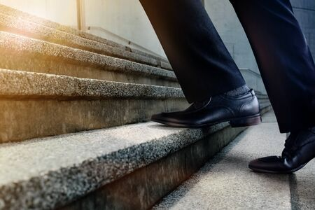 Motivation and challenging Career Concept. Steps Forward into a Success. Low Section of Businessman Walking Up on Staircase. Male in Black Formal Dress Stock fotó