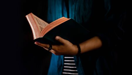 Reading Concept. Person Holding Opened Bible Book on Hand. Dark Tone, Cropped image Stock fotó