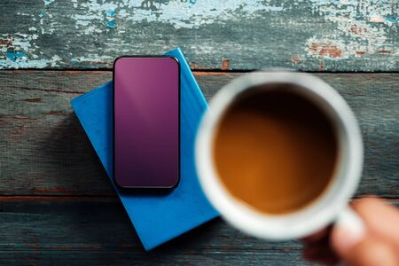 Smartphone Mockup Image  . Using Mobile Phone while Drinking Coffee and Reading Book