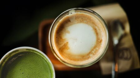Closeup of Hot Coffee Latte and Matcha Green Tea in Cup on Table. Top View. Cafe or Restaurant Scene