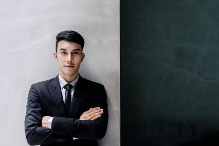 Portrait of Young Confident Businessman in Black Formal Suit. Standing by the Wall, Crossed Arms and Looking at Camera