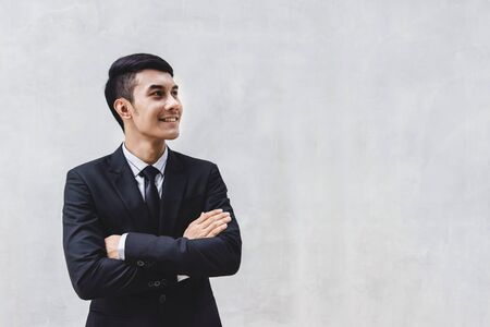 Portrait of Happy Businessman in Black Formal Suit. Standing by the Wall, Crossed Arms and Looking away Stock fotó