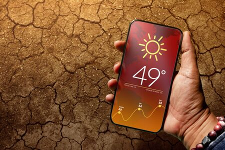 Ecology and Technology Concept. High Temperature Weather show on Mobile Screen on Hot Sunny Day. Top View, Dry Cracked Earth with Hard Sunlight as background