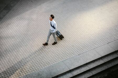 Happy Young Businessman Walking with Suitcase in the City. Modern Male in Business Trip. High Angle View. Full Length 版權商用圖片