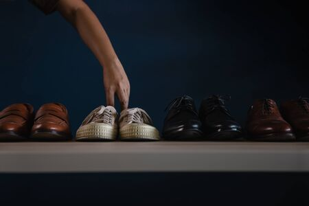 Men Footwear Fashion. Male Picking a Sneaker Shoes to Wearing. Quit a Job or be Balanced Relaxation Concept