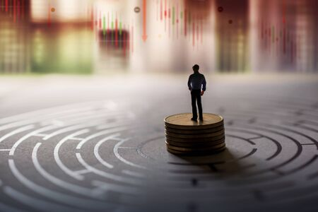 Vision of  Leader in Financial or Economy Crisis Concept. Stock Marketing Graph is going Crash and Down. Miniature Figure of Businessman standing on Money Coin Stack at the center of Maze and Looking Forward