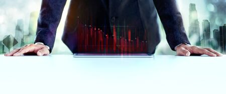 Financial or Economy Crisis Concept. Business Leader. Stock Marketing Graph is going Crash and Down. Professional Businessman with Low Profit Graph on Tablet. Double Exposure Image of Urban Building as background