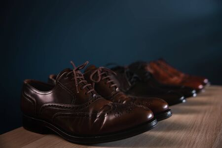 Men Footwear Fashion. Variety of Male's Shoes on Shelf in House. Formal Leather Shoes, included Wingtip, Loafer and Oxford