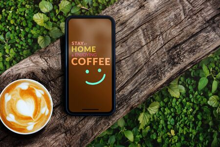 """Covid-19 or Corona Virus Situation Concept. Message """"Stay at Home and Enjoying Coffee"""" showing on Mobile Phone. Positive Mind. Top View"""