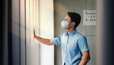 Quarantine at Home for Covid-19 Concept. Young Man with Surgical Mask Standing by Window in the House. Waiting to go Outside. Positive Mind