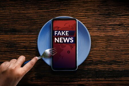 Fake News Concept. Reading Daily Fake News from Mobile Phone or Social Media Like Eating  Breakfast in every morning. Metaphor Stock Photo