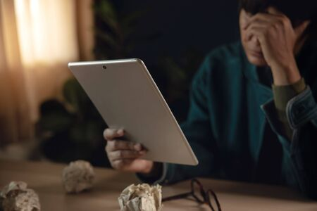 Tired and Stressed Person Sitting on Desk with Tablet in House. Hand on head. Depressed from Work or Some Crisis