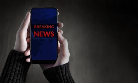 Breaking News Headline Showing on Mobile's Screen. Person Using a Smartphone to Checking News and Update. Top View Stock Photo