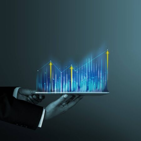 Technology, High Profit, Stock Market, Business Growth, Strategy Planing concept. Businessman in Suit Presenting High Graphs and Charts Information on Digital Tablet