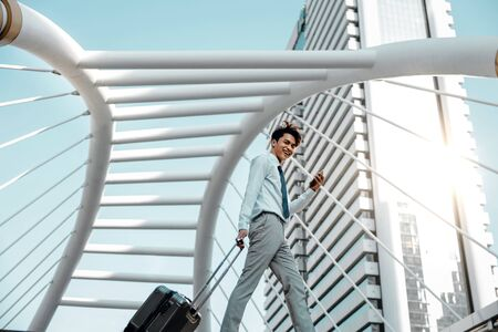 Happy Young Businessman Using Mobile Phone while Walking with Suitcase in the City. Lifestyle of Modern People. Low Angle View. Full Length. Modern Urban City as background