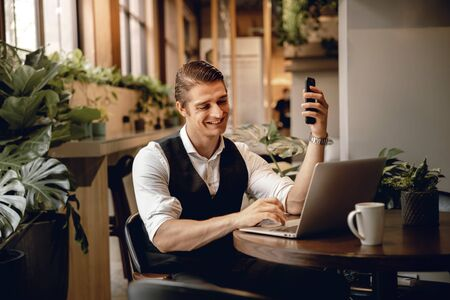 Smiling Businessman Working on Computer Laptop in Creative Working Space or Cafe