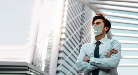 Covid-19 Situation in Business Concept. Businessman with Surgical Mask standing in the City. Protected and Care of Health. Stressed out due to Corona Virus. Looking up into the Sky
