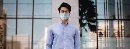 Covid-19 Situation in Business Concept. Businessman with Surgical Mask standing in the City. Protected and Care of Health. Stressed out due to Corona Virus. Looking at Camera