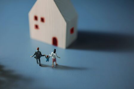 Happy Family Concept. Miniature Figure of Father, Mother and Son Holding Hands and Walking into the House