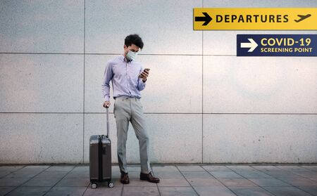 Corona Virus Situation Concept. Young Passenger Businessman wearing Surgical Mask. Using Smartphone. Standing with Luggage in the Airport. Departures Sign and Covid-19 Checkpoint as background