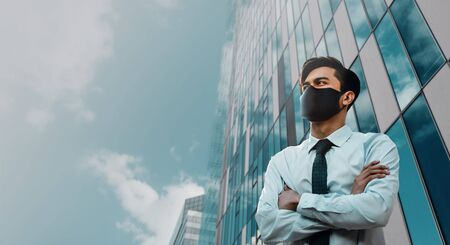 Covid-19 Situation in Business Concept. Businessman with Safety Mask standing in the City. Protected and Care of Health. Stressed out due to Corona Virus. Looking up into the Sky Stock Photo