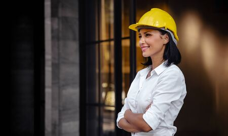 Portrait of a Confident Construction Engineer Woman. Smiling and Looking away. Standing in front of the Modern Office Building
