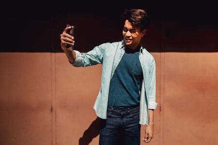 Portrait of a Happy Young Man Smiling while Using Mobile Phone to Taking Selfie. Lifestyle of Modern People. Standing by the Colorful Wall on Hot Sunny Day Stock Photo