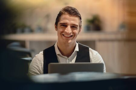 Smiling Businessman Working on Computer Laptop in Creative Working Space or Cafe. Headshot, Looking at the Camera