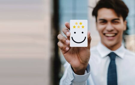 Customer Experiences Concept. Young Businessman Feedback a Happy Face Icon and Positive Review on Card. Client's Satisfaction Surveys Rating. Marketing Strategy Stock Photo
