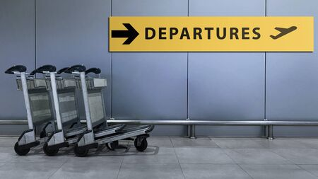 Airport Sign for Departures Terminal Directory inside the Building. Travel and Transportation Concept. Blurred Baggage Carts as foreground Stock Photo