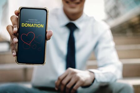 Online Donation Concept. Smiling Businessman showing a Donate Message on Mobile Screen Stock Photo