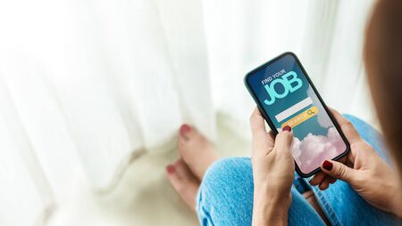 Unemployment Concept. Woman Sitting at Home and Using Online Job Searching Website via Mobile Phone to Finding a New Job Imagens - 150499894