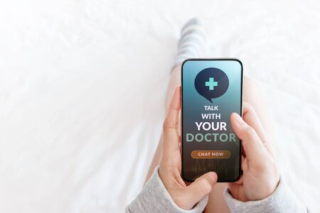 Helathy Lifestyle and Technology Concept. Modern Person Using Online Medicine Application via Mobile Phone to Request a Consultation from the Doctor. Lying in Bed using Smartphone in Top View