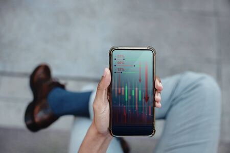Financial or Economy Crisis Concept. Business Leader. Stock Marketing Graph is going Crash and Down. Professional Businessman seeing Low Profit Graph on Mobile Phone Imagens