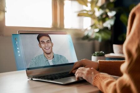 Working From Home Concept. Online Meeting for Small Business Partnership. Young Employee Woman making a Video Call to Talking a Business Topic with her Smiling Man Partner via Computer Laptop. Side View Stock Photo