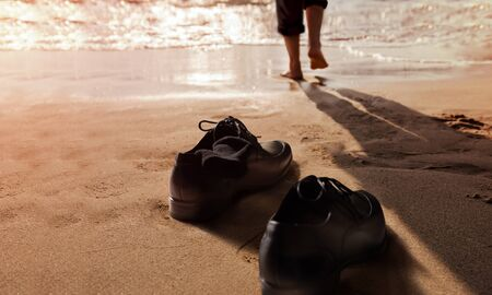 Work Life Balance Concept. Businessman take off his Working Shoes and leave it on the Sand Beach for Walk into the Sea on Sunny Day. Low angle View. Quite a Job or Leaving from a Hard Work and Responsibility