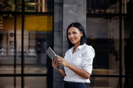 Portrait of a Smiling Mixed Race Business Woman, Using Tablet outside the building. Looking at the Camera