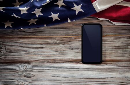 4th of July or Memorial Day of United States Concept. Blank Mobile Screen for Mockup. USA Flag Lying on Wooden Background. American Symbolic. Top View Imagens