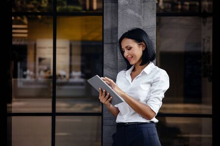 Portrait of a Smiling Mixed Races Business Woman, Using Tablet outside the building Imagens - 149980723