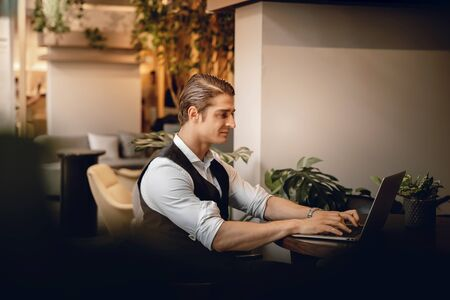 Smiling Businessman Working on Computer Laptop in Creative Working Space or Cafe Imagens - 150066279
