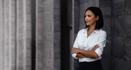 Portrait of a Smiling Mixed Races Business Woman, Crossed Arm and Looking away in Urban City Imagens - 150066280