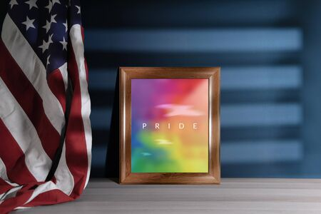 Gay, Homosexual, LGBTQ in USA Concept. Rainbow Color picture with Pride Text in Photo Frame. United States of America Flag Hanging on the Wall