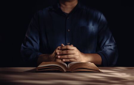 Spirituality and Religion Concept, Person Sitting on Desk to Making Pray on a Holy Bible in Church or House. Believe and Faith for Christian People Imagens - 150196447