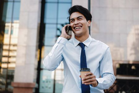 Portrait of a Happy Smiling Businessman Talking on Mobile Phone in the Urban City. Lifestyle of Modern People. Modern Building as background Imagens - 150066283