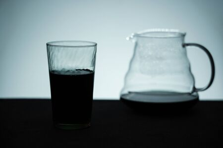 Silhouette Image of Coffee. a Glass with Black Coffee and a Server on Table