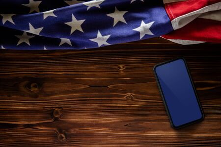 4th of July or Memorial Day of United States Concept. Blank Mobile Screen for Mockup. USA Flag Lying on Wooden Background. American Symbolic. Top View Imagens - 149744521