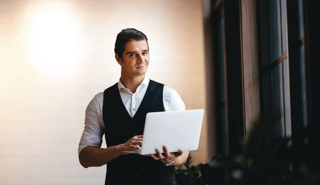 a Young Caucasian Businessman Working on Computer Laptop in the Modern Workplace. Smiling Businessman Standing by the Window and Looking into the Camera