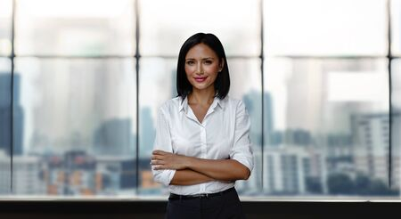 Portrait of a Smiling Mixed Races Business Woman, Crossed Arm and Look into the Camera. Blurred Office Building in the City as background Imagens - 150260170