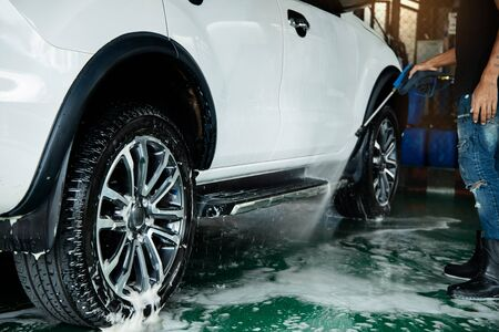 Manual Car Wash. Man using High Pressure Water Machine and Soap to Cleaning Car. Focus on Wheel Imagens